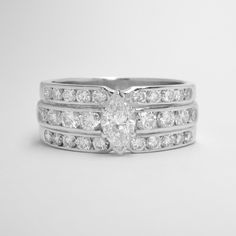 A triple banded channel set round brilliant cut diamond ring, mounted in palladium and platinum with a 0.41ct. 'D' colour, VS1 clarity marquise diamond claw set in the centre. Marquise Diamond, Dress Rings, Clarity, Diamond Cuts, Centre, Channel, Silver Rings, Wedding Rings, Engagement Rings
