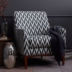 This chair is a solid and comfortable piece of furniture supported on solid wooden legs. The seat and backrest are filled with soft materials for enhanced comfort. The striped black and white pattern is ideal for different colour stylizations.