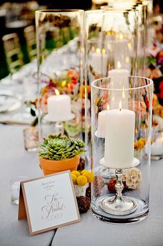 The bridal banquet table is decorated with tall hurricanes, lush succulents, scabiosa pods, wicker balls and craspedia.