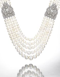 Important and very fine natural pearl and diamond necklace, Cartier, 1930s Composed of five graduated rows of natural pearls, measuring from approximately 3.75 to 12.05mm, set to the sides with two shield-shaped plaques, set with circular- and single-cut diamonds, length of shortest row approximately 453mm, signed Cartier and numbered.