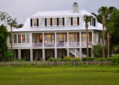 """Lowcountry style is in the smaller  details. """"There are so many things that make a home distinctly Charleston, but the shutters are what does it on this home,"""" says interior designer Alix Bragg. """"The old-school style of the louvered shutters (painted Charleston green) is a staple in the Lowcountry.  Of course, the palm trees and metal roof give it away too!"""""""