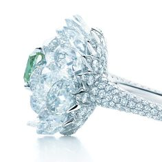 A ring with a fancy vivid green diamond surrounded by rose-cut and round white diamonds.