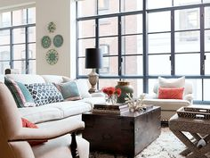 New York apartment with floor to ceiling black trimmed windows, a large trunk serving as a coffee table, white sofa with ikat print pillows, and dueling arms chairs