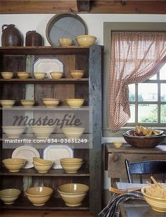 https://image1.masterfile.com/getImage/834-03831249em-COLLECTION-DISPLAYS-Primitive-display-cupboard-full-of-Yellowware-bowls-of-all-sizes.-In.jpg
