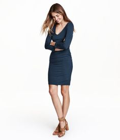 Short, fitted jersey dress with long sleeves and a V-neck. Elastication at side seams to create gathers at waist. Lined.
