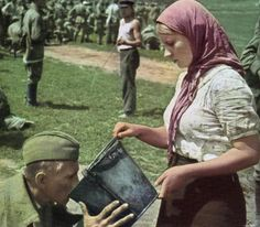 A soviet soldier is given water by a Ukrainian woman after being captured. [World War II, 1941]