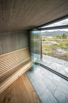 A custom-made slatted-timber bench wraps around two sides of the room and provides seating that looks out through the large openings towards the mountains and lake.