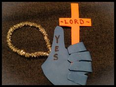 """Say """"Yes, Lord"""" Craft. Materials needed: two colors craft foam, sharpie, glue gun and pipe cleaner. Trace and cut hand out of one color foam sheet and cut out a cross out of the other color(make sure your cross is a bit long at the bottom so you have more to work with in the hand). Glue fingers over onto the palm to make a """"thumbs up. """". Glue the cross inside the closed fingers. Make a hanger out of the pipe cleaner and glue to the back. Write the words on the front with a sharpie."""