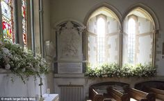 Brought to life: Flowers spilled out of window displays next to the pews in the historic c...