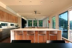 Interior, Inspiring Kitchen Interior Design With Big White Kitchen Islands With Wood Legs Stainless Steel Bar Stools Recessed Kitchen Lightings Commercial Interior Glass Doors With White Frame Wooden Wall Kitchen Cabinet Ceiling Fan: Perfect and Ideal Kitchen Interior Design Ideas