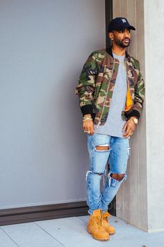 Big Sean wearing  Fear of God Camo Bomber Jacket, Fear of God Selvedge Denim Vintage Indigo Jeans, Timberland 'Six Inch Classic Boots Series - Premium' Boot