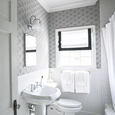 Black and white bathroom features upper walls clad in black and white fan shaped wallpaper, Cole & Sons Feather Fan Wallpaper, and lower walls clad in white beadboard trim lined with a curved pedestal sink under a frameless mirror illuminated by white glass downlight sconces.