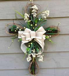 Grapevine Cross accented with faux greenery, berries, flowers and completed with a beautiful bow! The perfect addition to your home...also makes a great gift!