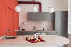 Cocina abierta al salón con muebles en color gris y peninsula en forma redondeada. Lámparas de techo globo con detalles en latón. #cocinas