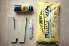 DIY Concrete Letter  hollow cardboard letter (available at your local craft store) box cutter breathing mask (or something to cover your nose so you don't breath concrete dust) disposable gloves two plastic spoons two disposable plastic bowls a disposable cup concrete mix cement color water