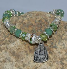 """This pretty bracelet was made with green and jade Swarovski crystal, colorful rhinestone silver plated spacers and a Happy Birthday cake charm with a small Wish charm accompanying it. Perfect for anyone who loves green and it also can be an August (Peridot) birthstone bracelet. A sparkly birthday present for someone special. """"May you live as long as you want and never want as long as you live."""" - Irish Blessing"""