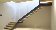 stair constructed in powder coated mild steel carriage, toughened glass balustrade and hardwood timber treads