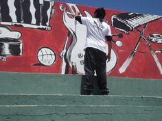 FOTOGRAFIA SIN ROSTRO: un chico pintando un muro con imágenes de música, es una imagen que nos habla de un proceso creativo, de inspiración, arte en si mísmo y un mensaje que construye ciudadania. No importa su nombre, identifica a los jóvenes en su gran potencial.