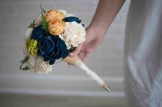 To capture the bliss of Coastal Charm, you need this 24 forever flower bouquet in your home. You'll see just how darling it looks with these coastal inspired color scheme, and soft white flowers - the perfect accompaniments to a picturesque home! Made from two dozen forever flowers. Wrapped in twine & lace! Colors: Natural White, persian blue, & sunny yellow.
