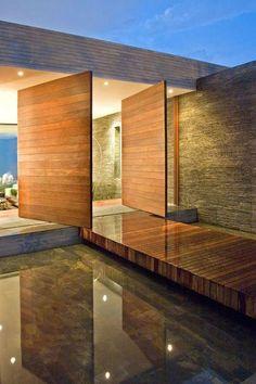 Portas pivotantes de madeira na entrada de uma casa de arquitetura moderna.  Fotografia: http://www.decorfacil.com/portas-pivotantes/