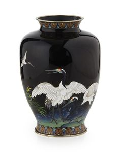 <b>JAPANESE CLOISONNÉ VASE</b> <br /> SIGNED SUZUKI, MEIJI PERIOD <br /> the oviform body decorated with an auspicious flock of red-capped Manchurian cranes depicted mid-flight and amongst reeds on black ground, with lappets to the neck and foot, capped on the rim and foot ring with white-metal bands inscribed Suzuki <br /> 25cm high Japanese Vase, Japanese Porcelain, Herons, Birds 2, Japanese Beauty, Porcelain Vase, Metal Bands, Vases, Glass Art