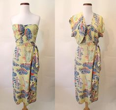 Rare 1940s Hawaiian Sarong Dress w/ Matching Bolero by Surfriders Sportswear Made in Honolulu!    This is absolutely the best vintage Hawaiian rayon print I have ever come across! It has images of surfers, diamond head, outrigger canoes, and sunsets all on a background of buttery yellow. The bodice of the dress is strapless with elastic ruching at the center. The skirt wraps over to one side with a swag at the hip, and a belt ties across at the hips to finish the look. Metal zipper on the…