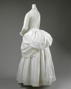 An 1885 white openwork bustle dress