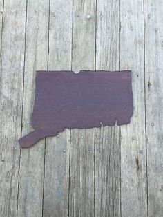 """This state of Connecticut wall hanging is hand cut from old salvaged tin.  It is sealed with shellac to give it a beautiful sheen to it.  The state measures 15"""" wide and 10 1/2"""" tall.      This item is available in 3 different options:      1.  you can purchase just the tin state, no hangers or attached to wood, $20      2.  Attached to a whitewashed distressed 3/4"""" pine board (see picture of state of Texas), $45      3.  Attached to burlap wrapped pine board (see picture of the state of…"""