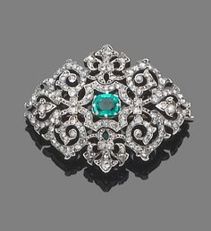 A late 19th century emerald and diamond brooch  The fine openwork rose-cut diamond cartouche, centrally-set with a cut-cornered step-cut emerald, mounted in silver and gold, length 3.8cm.