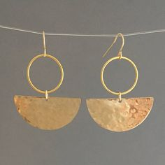 Hammered 14k gold fill half discs hang from circle hoops and earwires. Earrings from top of earwire measure 1.75 inches long and 1.25 inches wide. Also available in a sterling silver option with sterling silver earwires. Comes packaged in a small jewelry box.