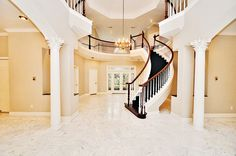 I like this foyer. The columns, the dark wood and the staircase. I wish it had a bigger/better chandelier though. Double Staircase, Spring Branch, Nottingham Forest, Columns, Dark Wood, Foyer, Sweet Home, New Homes, House Ideas