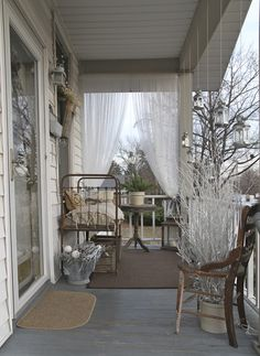 Elegantly furnished verandah with antique wrought iron bed and romantic white sheer curtains tied back.