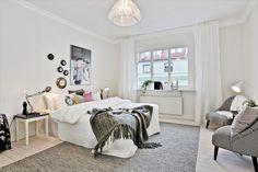 foteliki z tapicerką w pepitkę,szary tkany dywan,nowoczesne grafiki i kolorowe poduszki na białym łóżku w sypialni skandynawskiej - Lovingit.pl