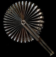 This black Victorian cockade fan dates to the mid 19th century and has charming die-cut leaves. It measures about 8.5 inches long and 8 inches in diameter when fully opened. There is some slight splitting in between the leaves, but the fan is in no immediate danger of tearing. I would recommend keeping it closed, rather than displaying it open to keep it in good condition.
