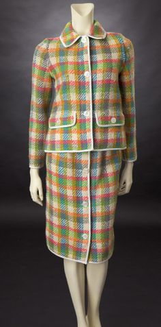 1960s Bonnie Cashin multi-colored tweed suit trimmed in white leather. The colors are orange, turquoise, green, gold, blue, gray and ivory. The tweed is woven in a plaid pattern. Large white buttons close the center front of the jacket and slim skirt.