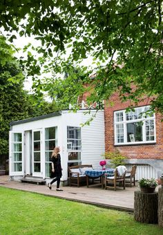 The house is surrounded by a large terrace with small tiles and wooden garden furniture.