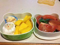 Hatching chick bento with hard boiled egg, banana pudding, mango, spinach and tomato salad.