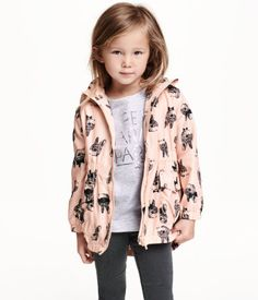 Patterned parka in soft woven fabric with a detachable, lined hood. Zip at front, front pockets with flap and snap fastener, elasticized seam at waist, and elastication at cuffs and hem. Lined.