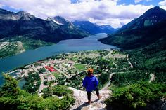 Hiker overlooking Waterton town, Waterton Lake and Canadian Rockies from Bear Hump. Waterton Lakes National Park, National Parks, Places To Travel, Places To Visit, Alberta Travel, Canadian Rockies, Lonely Planet, Montana, Places Ive Been