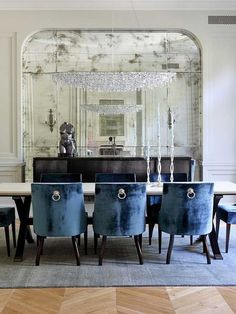 Very Unique Dining table set up . Love the classic mirror and the blue chairs ..