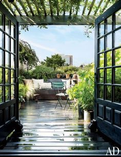 A rooftop garden in New York City is outfitted with French doors and bistro chairs.