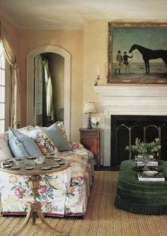 Peachy walls, chintz covered couch, hunter green velvet ottoman with silk cord fringe, sisal rug, and pony portrait above the fireplace - hunt country loveliness by Suzanne Rheinstein.