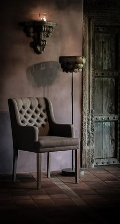 Architectural door adds a bold statement. Could be wall mounted for a special effect. Distressed accent wall adds a flair of subtle lighting. Candle scone adds a hint of mystery. Torchiere lamp adds dimension and chair is scaled properly to the actual living room space of the property.