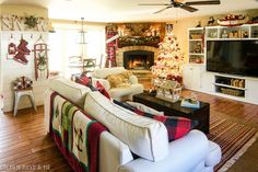 Cozy lodge style family room Christmas decor with stone fireplace, vintage snowshoes and toboggan