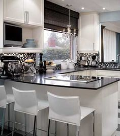 Candice Olson    Love this shiny, bright white & black kitchen design with crisp white kitchen cabinets, sleek black granite counter tops, kitchen peninsula and black & white glass tile backsplash! Love the natural roman shade, crystal chandelier and white leather modern counter bar stools