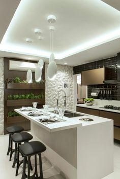 cuisine blanche et grise, avec des chaises de bar noires, îlot en blanc et gris, des luminaires blancs suspendus en forme ovale, un mur en revêtement en bois PVC couleur marron clair avec des pots de plantes vertes