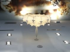 """FLOS Zeppelin Chandelier At the Pandora store at the Charlotte Airport Designed by Marcel Wanders Zeppelin pendant lamp providing diffused lighting. Steel structure sprayed with """"cocoon"""" resin. """"Candles"""" in PMMA and a crystal globe located at the center for a sparkle effect.  http://www.brandlighting.com/flos_taraxacum_cocoon_zeppelin.html With multiple recessed lighting."""