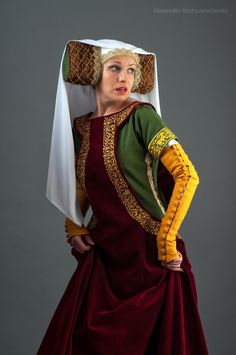Medieval sleeveless surcoat.  It is worn over a cotte as an obligatory garb for a solemn events. As it were an attire of aristocracy this garment were produced of noble materials such as velvet or brocade. In this case surcoat have been made to order from velvet of red wine colour and decorated with golden machine embroidery. The garment has a wide neck and deep, down to hips, armholes, through which undergarments were seen.