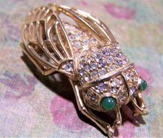 Mid Century Ciner cicada bug brooch Crystal rhinestone encrusted body, with green glass cabochon eyes, openwork wings Gold tone body Signed Ciner  1 7/8 x 1 inch Very good ... #gotvintage