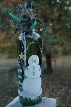 Let it Snow!  Sweet little snowman - hand painted on this wine bottle complete with ever greens and birch trees and falling snow.  Vintage looking silver tinsel on the bottle tied with vintage looking berries and tiny red jingle bells and a shiny green bow with a hint of little red dashes on it.  Asking $20 each.  If interested - please contact me, thanks!